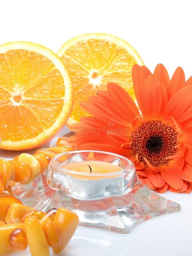 Apelsinen anmärker på en vit bakgrund: en orange gerberablomma, en bärnsten pryder med pärlor och stearinljuset - stilleben fotografering för bildbyråer