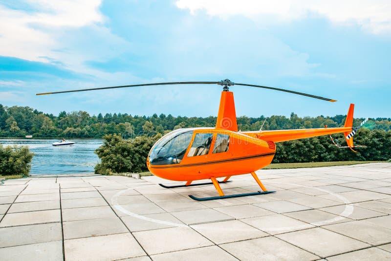 Apelsinen färgade helikoptern som parkerades på en konkret tjock skiva under blåa himlar royaltyfria foton