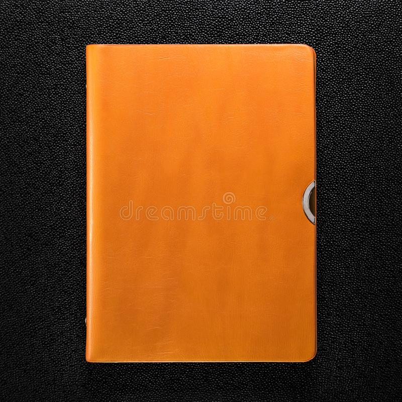 Apelsinen piskar boken på mörk bakgrund Främre sikt av hardcoverboken royaltyfri bild
