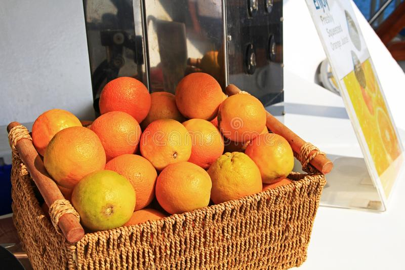 Apelsiner bredvid en nya sammanpressade orange Juice Machine royaltyfria foton