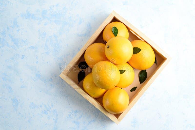 Apelsiner med sidor i ask P? en bl? tabell Fritt avst?nd f?r text Top besk?dar royaltyfria foton