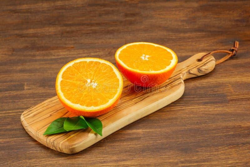Apelsiner med sidor på kitckenboard På en trätabell Fritt avstånd för text royaltyfri foto