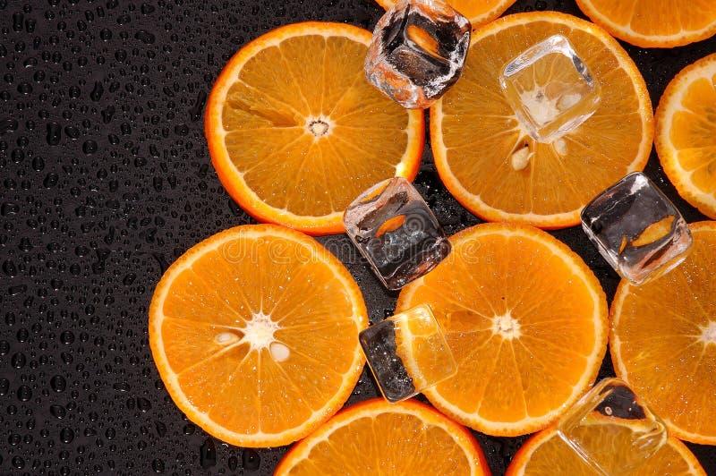 Apelsinskivor med iskuber fotografering för bildbyråer