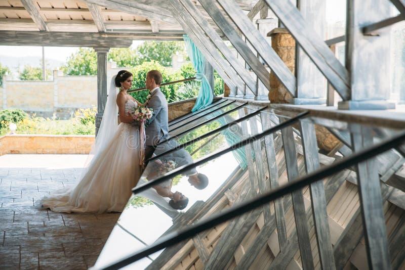 Apenas casal do noivo bonito em um terno de negócio cinzento e em uma noiva em um vestido branco luxuoso com um véu com foto de stock royalty free