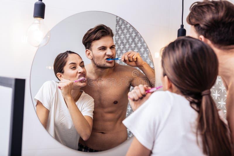 Apenas casal que faz as caras engraçadas que escovam os dentes junto fotos de stock