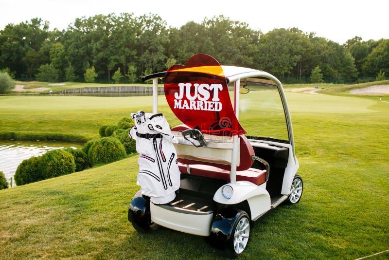 Apenas la muestra casada encendido apoya de un carro de golf imagenes de archivo