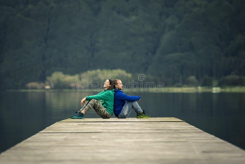Apenas la pareja de matrimonios joven se está sentando en el embarcadero por el lago volcánico imagen de archivo libre de regalías