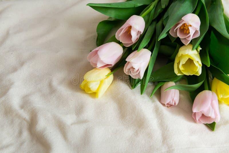 Apenas llovido encendido Ramo de tulipanes amarillos rosados en fondo beige de la tela El d?a de madre, d?a de San Valent?n y fel fotografía de archivo libre de regalías