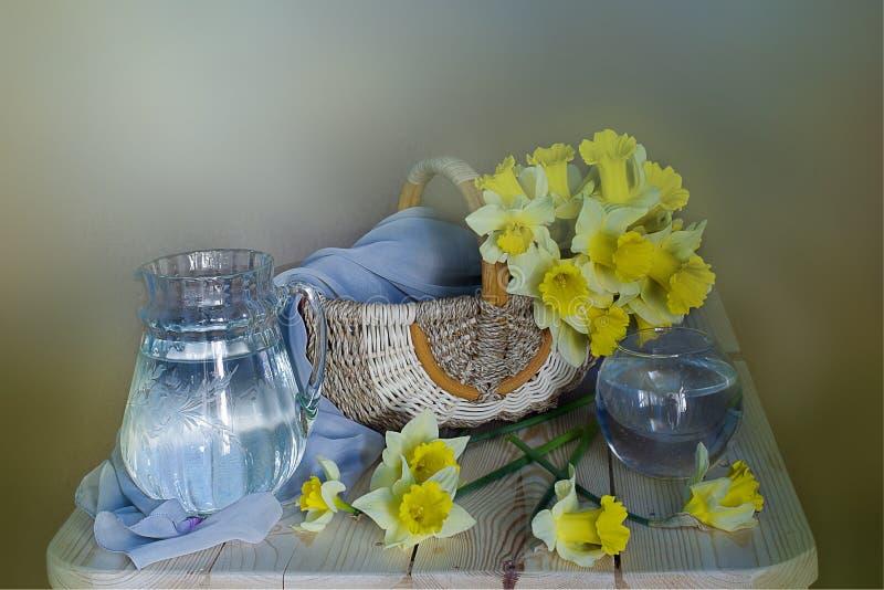 Apenas llovido encendido Todavía vida de narcisos amarillos en una cesta de mimbre, aislada en fondo amarillo claro imagenes de archivo