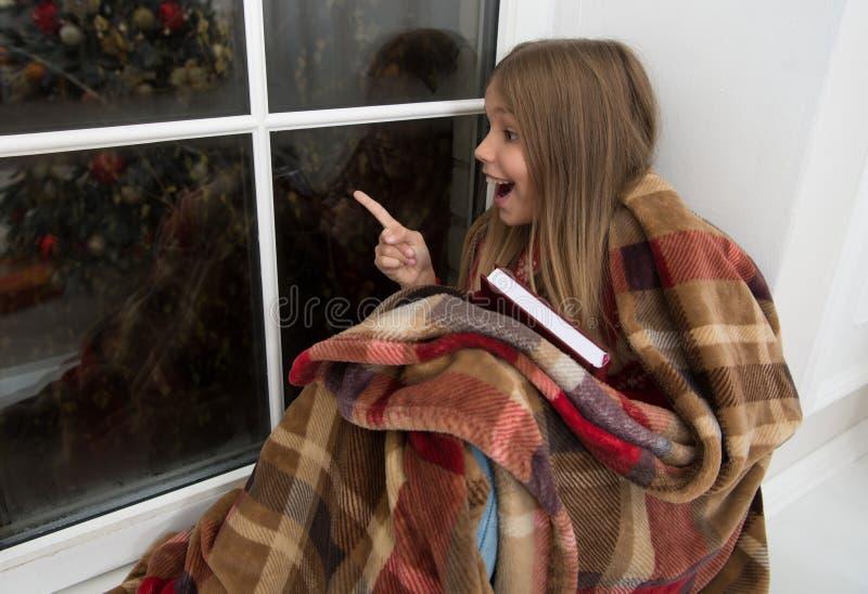 Apenas mire eso Pequeño finger feliz del punto de la muchacha en la ventana El pequeño lector goza el leer de historia de la Navi imagen de archivo libre de regalías