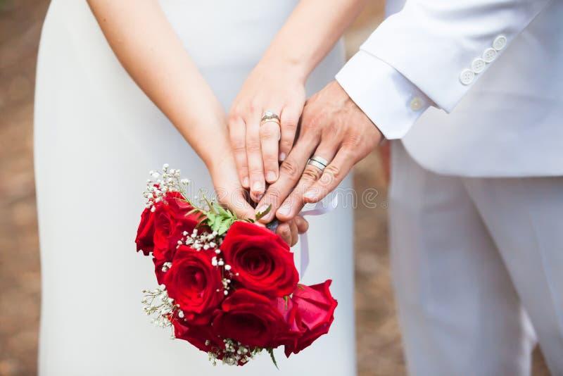 Apenas o casal compara suas alianças de casamento ao guardar cada outro as mãos do ` e um ramalhete fotografia de stock royalty free