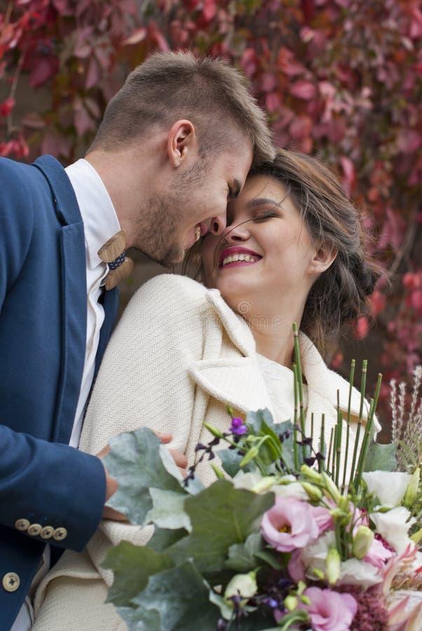 Apenas pareja cariñosa casada en el vestido y el traje de boda al aire libre en el ajuste de la ciudad contra la pared Risa feliz imagen de archivo libre de regalías