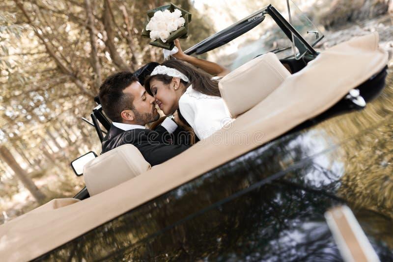 Apenas pareja casada en un coche viejo fotos de archivo libres de regalías