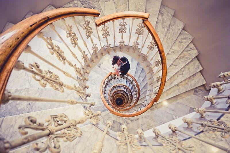 Apenas pareja casada en una escalera espiral foto de archivo libre de regalías