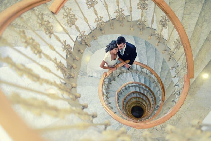 Apenas pareja casada en una escalera espiral fotos de archivo libres de regalías