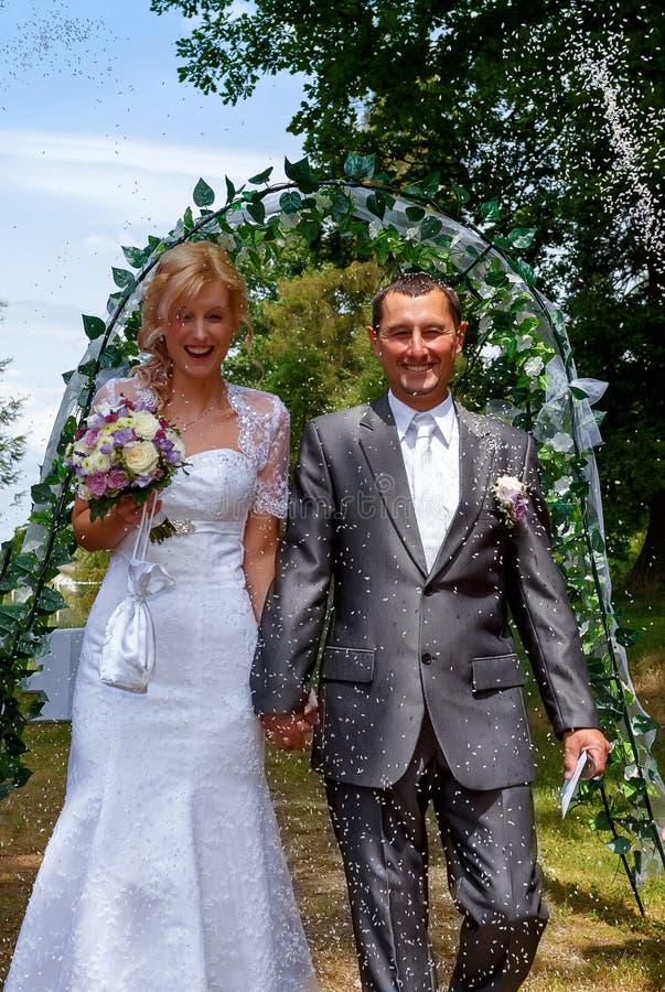 Apenas pareja casada feliz debajo de una lluvia del arroz foto de archivo libre de regalías