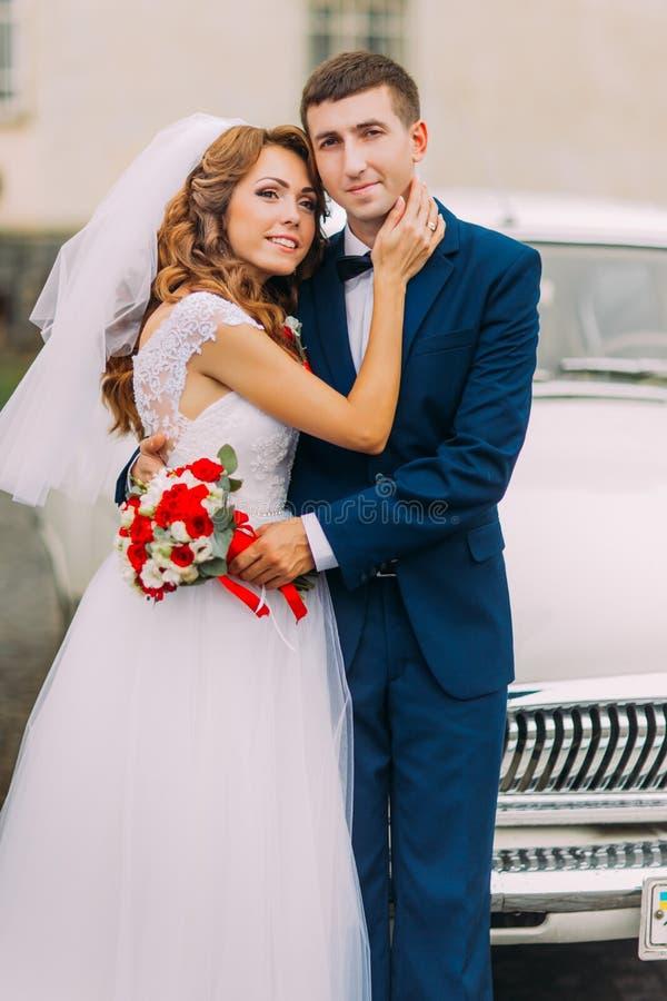 Apenas pareja casada feliz que presenta en el fondo del coche del vintage imagenes de archivo