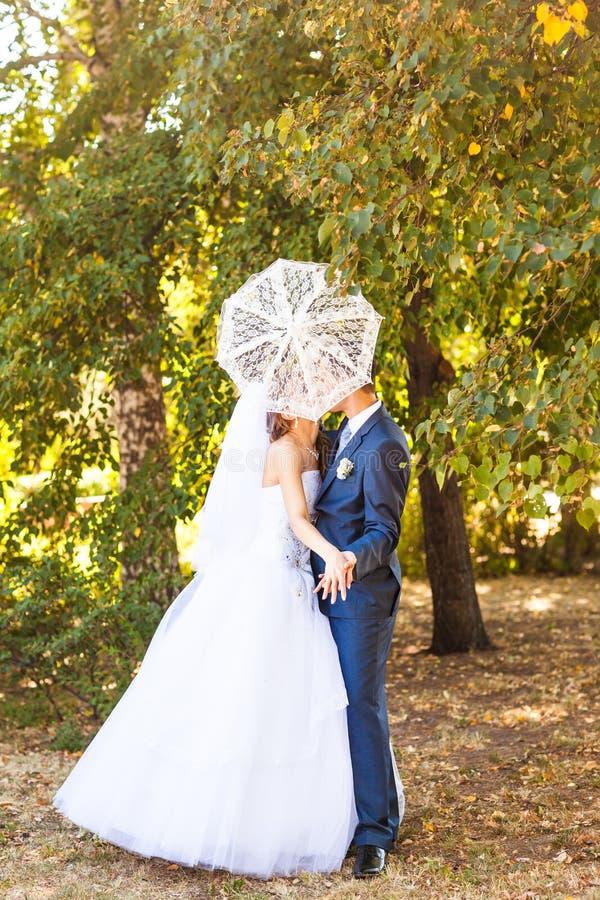 Apenas pareja casada que sostiene el paraguas blanco foto de archivo libre de regalías