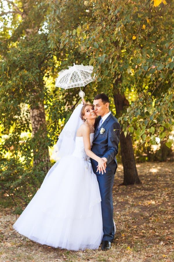 Apenas pareja casada que sostiene el paraguas blanco imagen de archivo libre de regalías