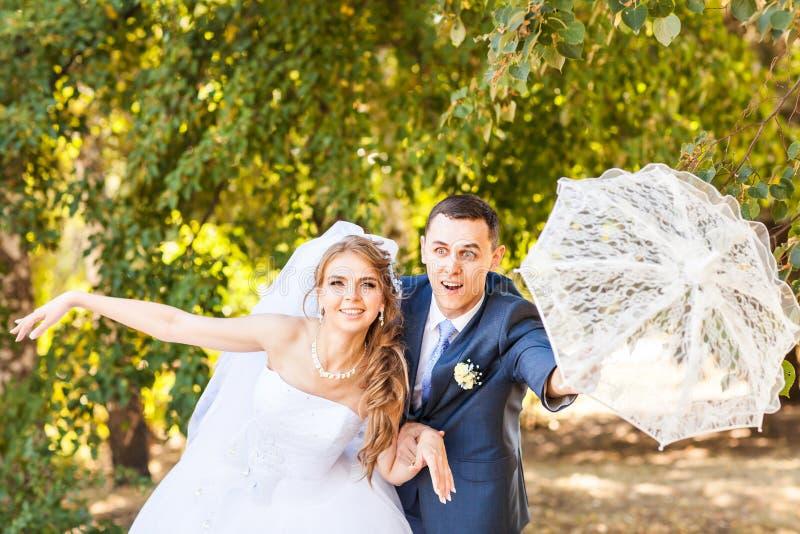 Apenas pareja casada que sostiene el paraguas blanco fotografía de archivo libre de regalías