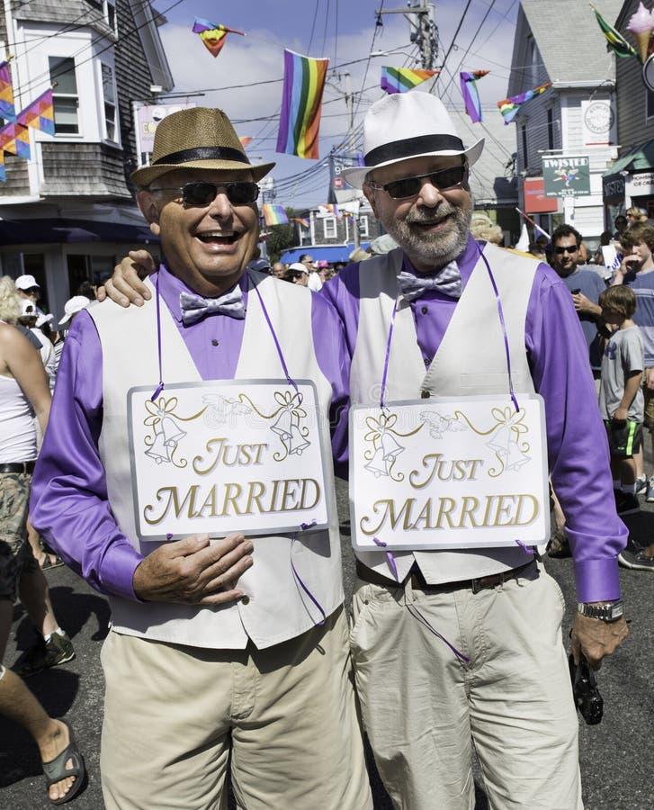 Apenas pares alegres casados que andam na 37th parada de carnaval anual de Provincetown em Provincetown, Massachusetts imagem de stock