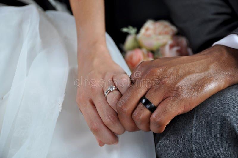 Apenas pares inter-raciais casados que guardam as mãos que vestem as alianças de casamento imagens de stock