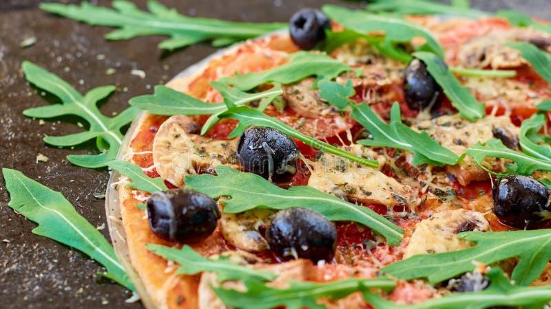 Apenas pizza quente cozida no fim preto do fundo acima Pizza do vegetariano com vegetais, azeitonas pretas e o rucola fresco imagem de stock royalty free