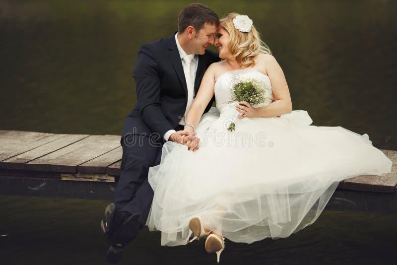 Apenas risa casada de la pareja mientras que se sienta con las piernas cruzadas en un b imágenes de archivo libres de regalías