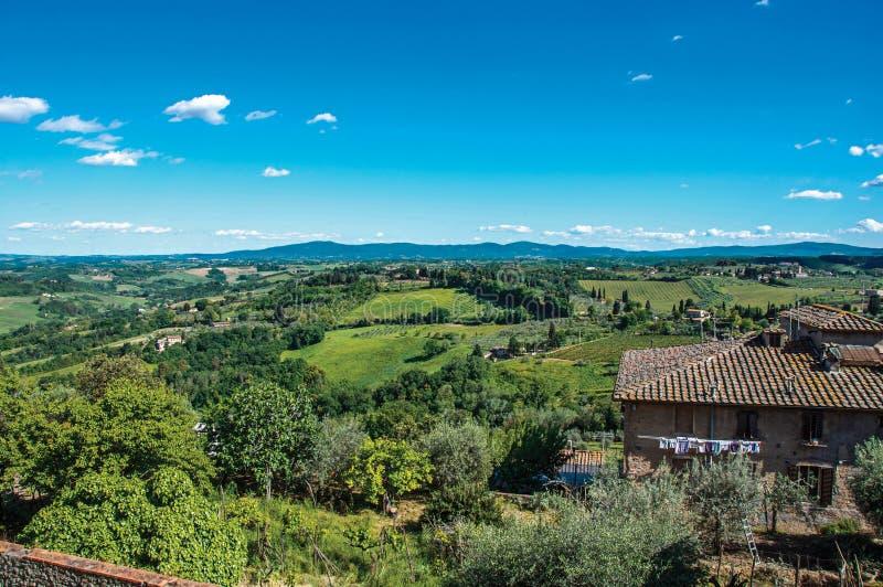 Aperçu de maison avec les collines toscanes vertes à l'arrière-plan et au ciel bleu à San Gimignano photos stock