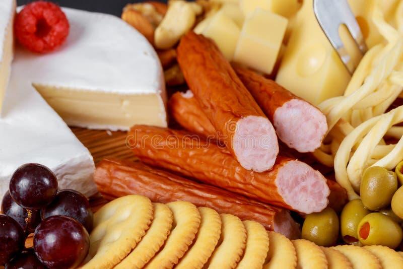 Aperitif-Brett mit Käsen, Cracker, Veggiesvielzahl des Fleisches stockfotos