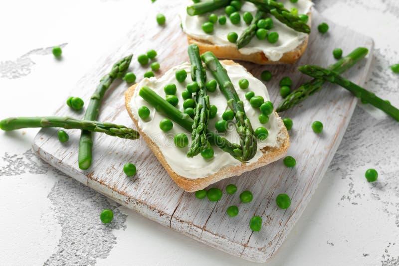 Aperitif bruschetta, Toast mit Spargel, Erbsen und sahniger Weichkäse auf weißem Brett lizenzfreies stockbild