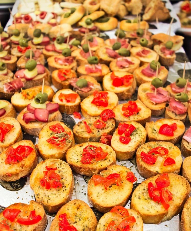 Aperitif bufet z zakąskami i bruschetta z pomidorami, oliwkami, kumberlandami i salami, obrazy stock