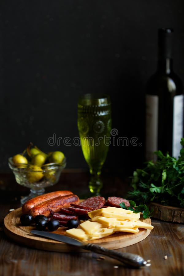 Aperitif table Meat snack, fried sausages, cheese, salami, olives and a glass of wine on a dark table. Menu and restaurant concept royalty free stock photography