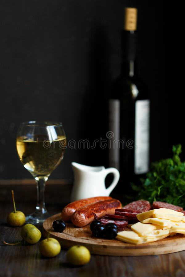 Aperitif table Meat snack, fried sausages, cheese, salami, olives and a glass of wine on a dark table. Menu and restaurant concept royalty free stock image