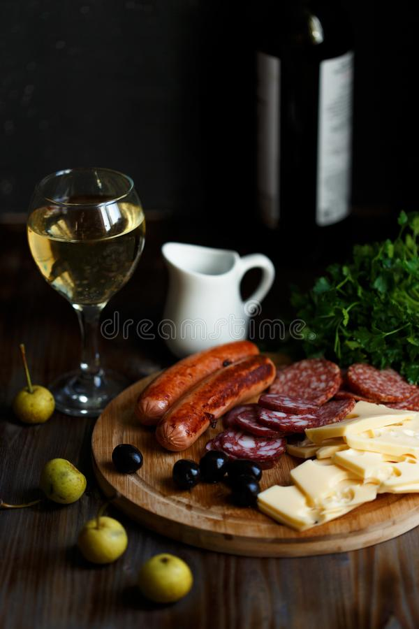 Aperitif table Meat snack, fried sausages, cheese, salami, olives and a glass of wine on a dark table Menu and restaurant concept. Close up royalty free stock photos
