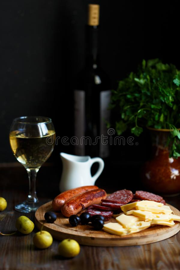 Aperitif table Meat snack, fried sausages, cheese, salami, olives and a glass of wine on a dark table Menu and restaurant concept. Close up royalty free stock image