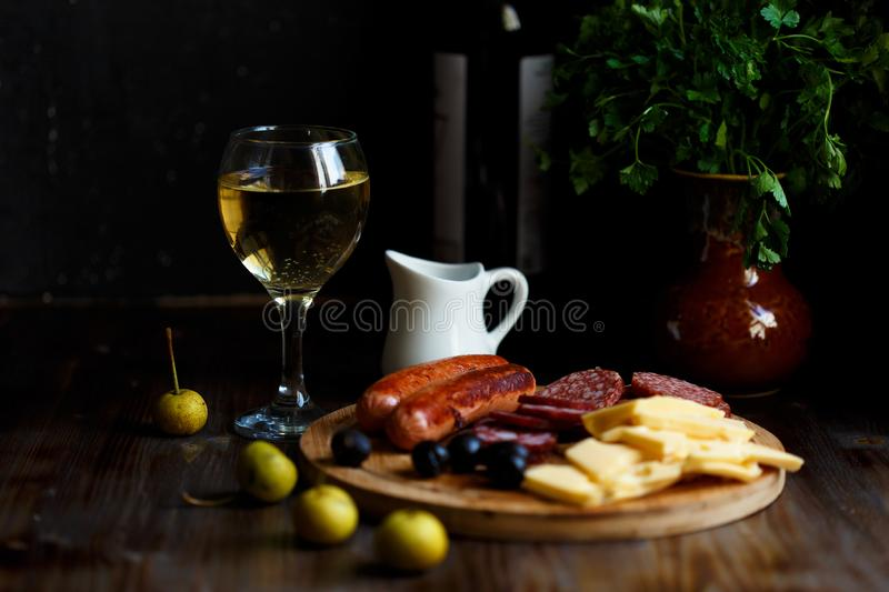 Aperitif table Meat snack, fried sausages, cheese, salami, olives and a glass of wine on a dark table Menu and restaurant concept. Copy space stock images