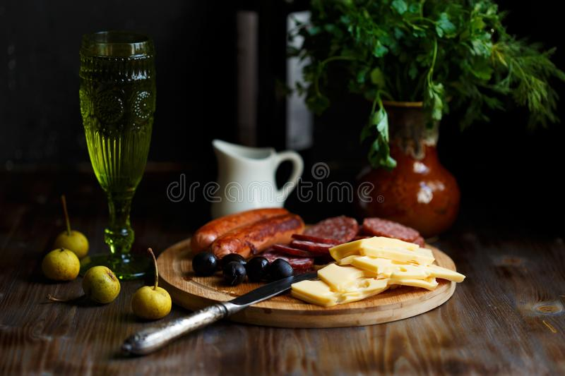 Aperitif table Meat snack, fried sausages, cheese, salami, olives and a glass of wine on a dark table Menu and restaurant concept. Copy space stock photos