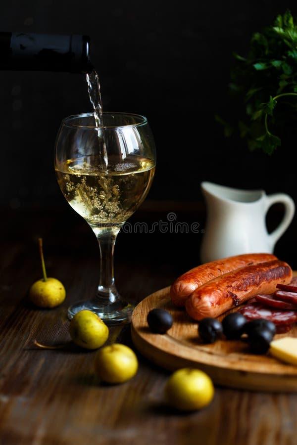 Aperitifkonzept Wein gießt in einen Glasbecher Auf dem Tisch Fleischaperitif, gebratene Würste, Salami, Käse, Oliven lizenzfreie stockfotografie
