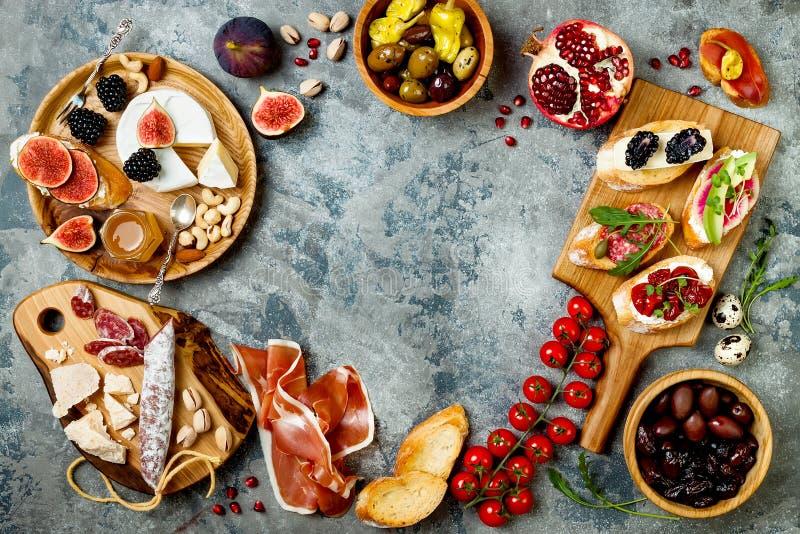 Aperitifs verlegen mit italienischen Antipastisnäcken Brushetta oder authentische traditionelle spanische Tapas stellten, Käsevie stockbilder