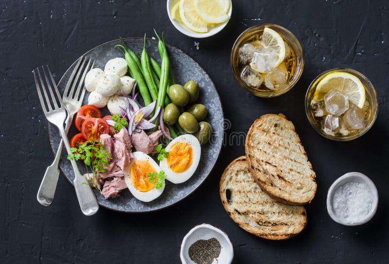 Aperitiftabelle - Platte des eingemachten Thunfischs, grüne Bohnen, Mozzarellakäse, Tomaten, kochte Ei, Oliven, gegrilltes Brot u lizenzfreie stockfotografie