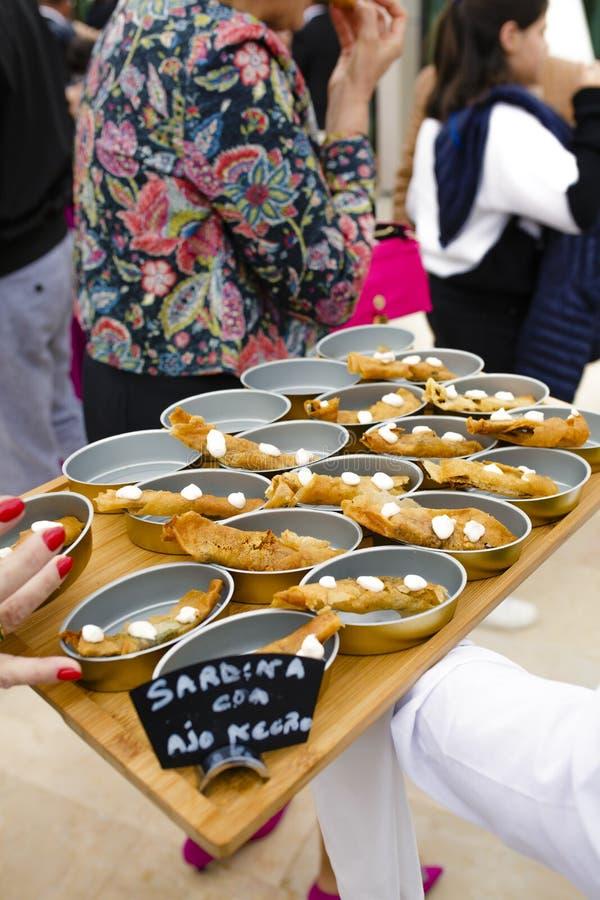 Aperitivi della sardina del servizio del cameriere con aglio nero immagini stock