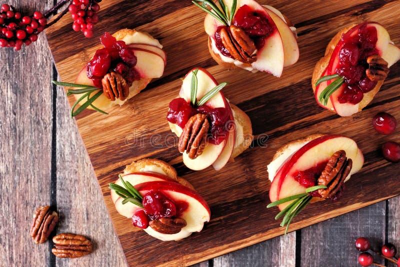 Aperitivi di Crostini con le mele, mirtilli rossi e brie, sopra su un vassoio di legno fotografia stock libera da diritti