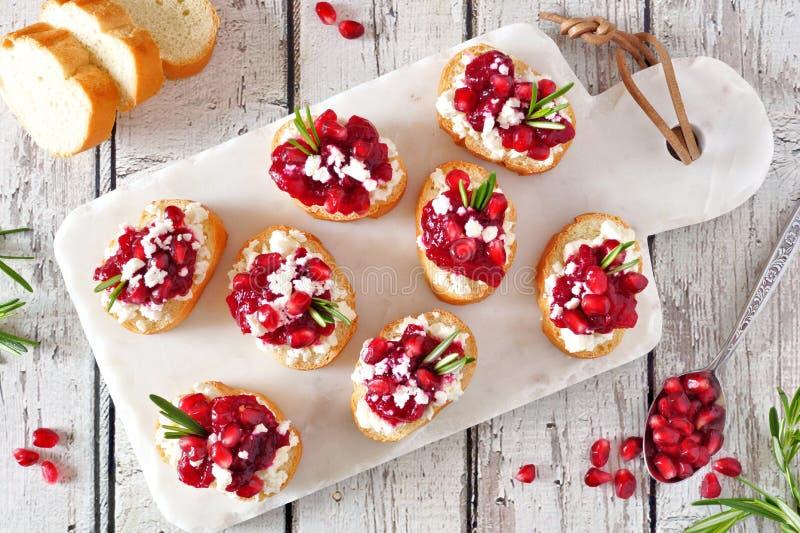 Aperitivi di crostini di festa con i mirtilli rossi, i melograni e la feta, vista superiore su un vassoio bianco immagini stock