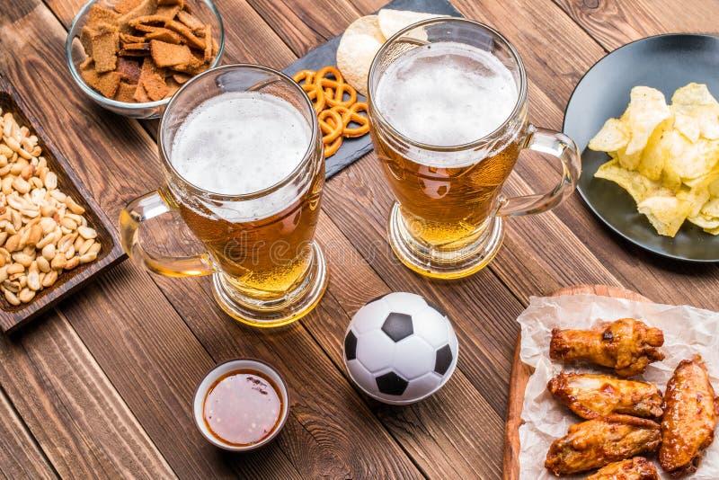 Aperitivi e birra sulla tavola per l'orologio la partita di calcio fotografia stock libera da diritti