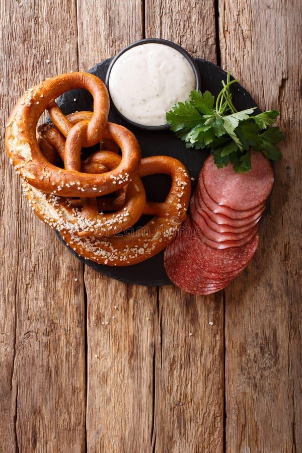 Aperitivo alemão: salame e pretzeis cortados com close-up do molho fotos de stock royalty free