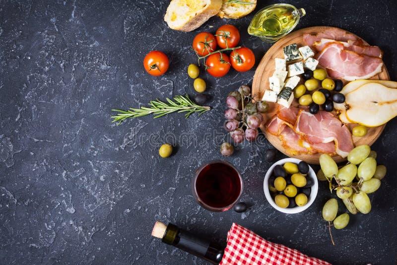 Aperitivo, antipasto italiano, presunto, azeitonas, queijo, pão, uvas, pera e vinho no fundo de pedra escuro Vista superior imagem de stock