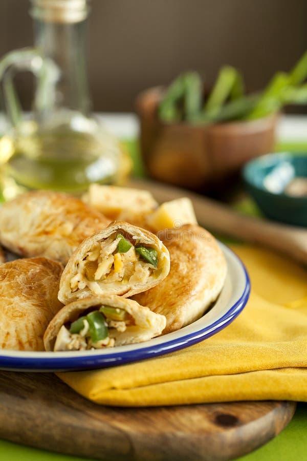 aperitivo caldo per la cena della famiglia torte cotte della pasta sfoglia farcite con il pollo, il formaggio, il pepe sul bordo  fotografia stock