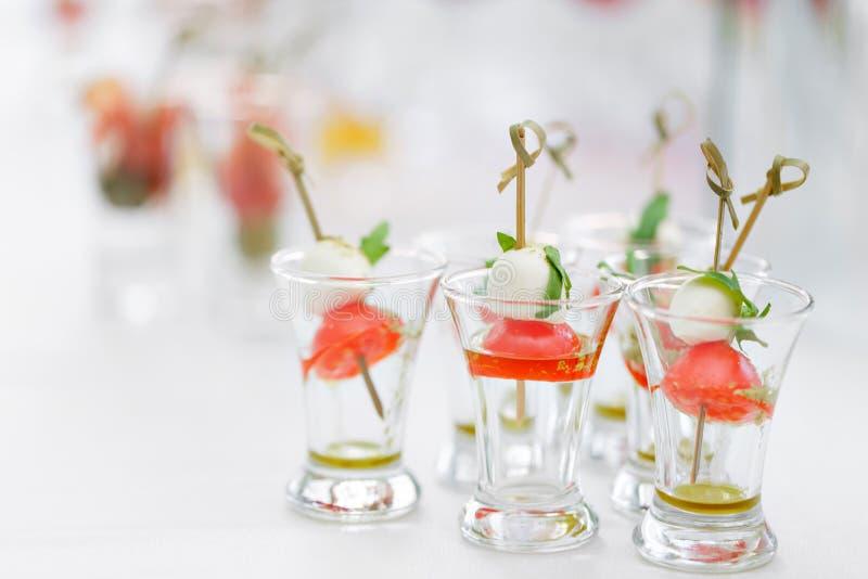 Aperitivo, Caprese Tomates, mussarela e manjeric?o de cereja em espetos Molho de Pesto Bufete no jantar de gala fotografia de stock