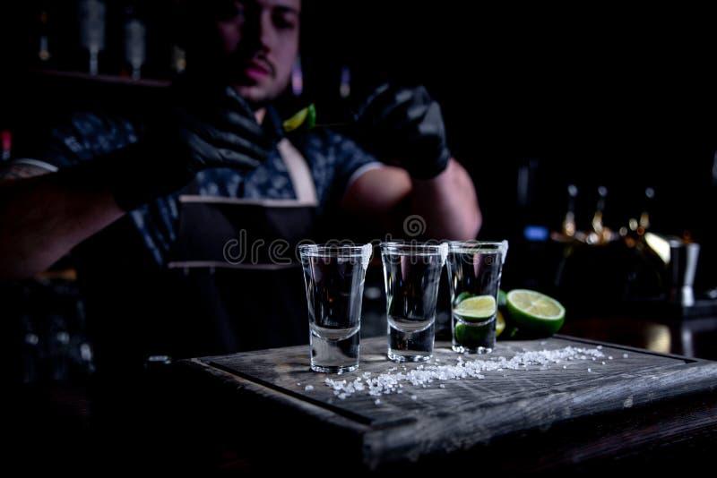 Aperitivo con los amigos en la barra, tres vidrios de alcohol con la cal y sal para la decoración Tiros del Tequila, selectivos fotos de archivo